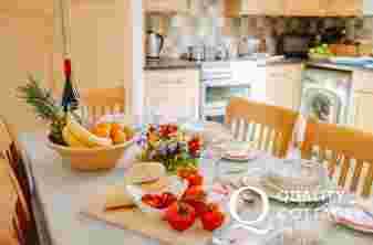 Kitchen table laid with fresh fruit and flowers