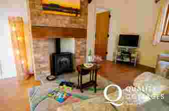 Lounge t.v. with sofa drinks table and gas log burner