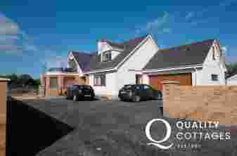 Exterior front of large luxury holiday cottage with ample parking and sea views in Four Mile Bridge, Anglesey.
