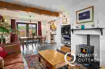 Living room of Worth House with log burner, sofa and dining table