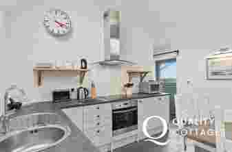 Kitchen-diner with open shelve, white units and modern kitchen appliances