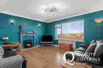 Spacious living room with 2 leather sofas, gas fire, TV, lamps and side tables