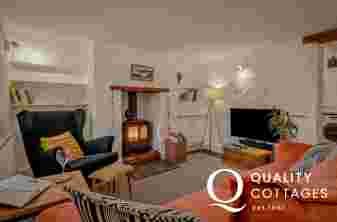 Holiday cottage in Bosherton, Pembrokeshire - lounge with sofa, armchair, TV and wood burner.