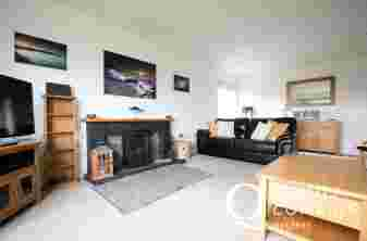 Holiday cottage on The Llyn Peninsula in Morfa Nefyn - lounge with log fire, TV, armchairs and leather sofa.
