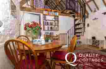 Traditional Pembrokeshire holiday cottage - living/dining room with spiral staircase to 'Crog Loft'