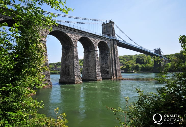 Menai suspension bridge was the worlds first large iron suspension bridge designed by Thomas Telford and completed in 1826. The first vehicle to go across was the London to Holyhead mail coach