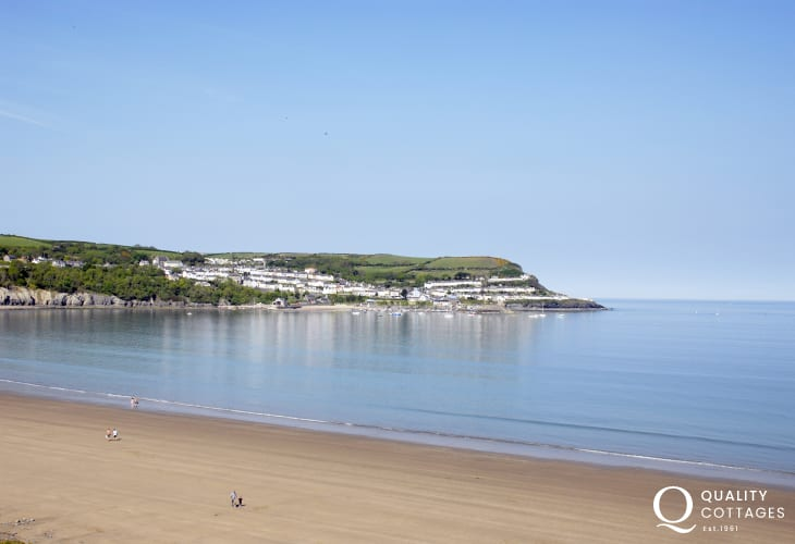 The golden sands of Treath Gwyn Beach (Blue Flag) sweeps round the bay to New Quay perched upon the headland