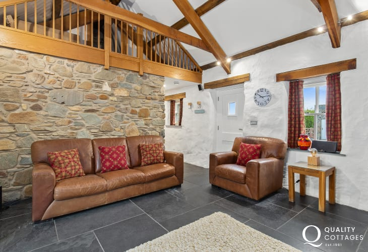 Stiting Room with large sofa, arm chair, stone walls and slate floors