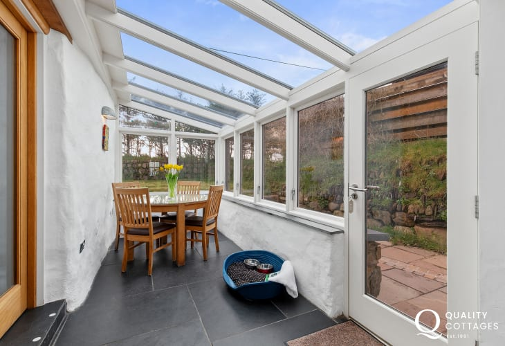 Dining Room conservatory with slate floors and dog bed