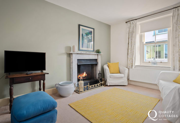 Separate sitting room with 3 seater & 2 seater sofa with footstool, TV and open log burning fire