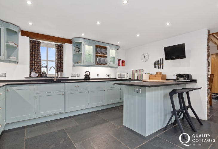 Duck egg shaker kitchen with slate floor and breakfast bar