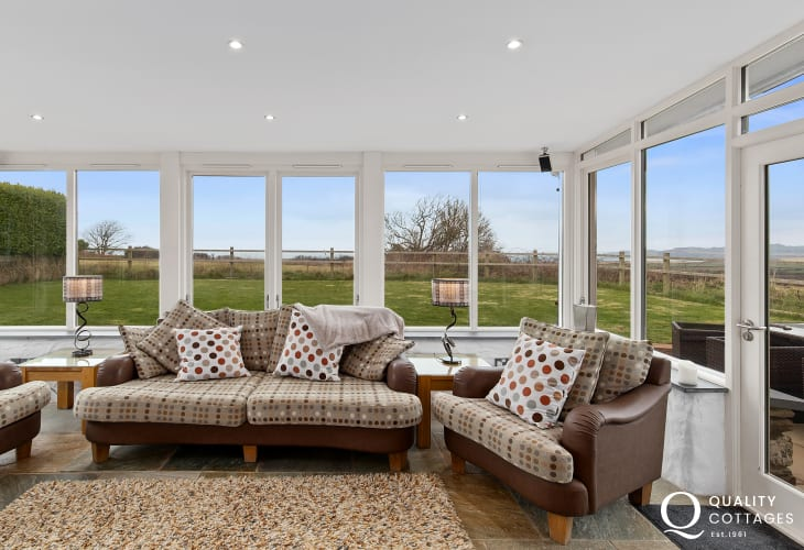 Living room with Melin Tregwynt and leather sofas with cushions bright room with coastal views