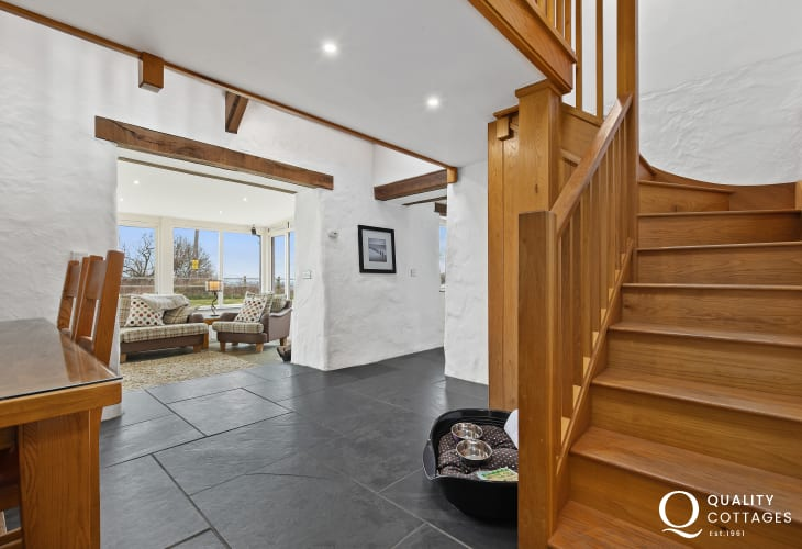 Oak stairway, dining area, dog bed and slate floor