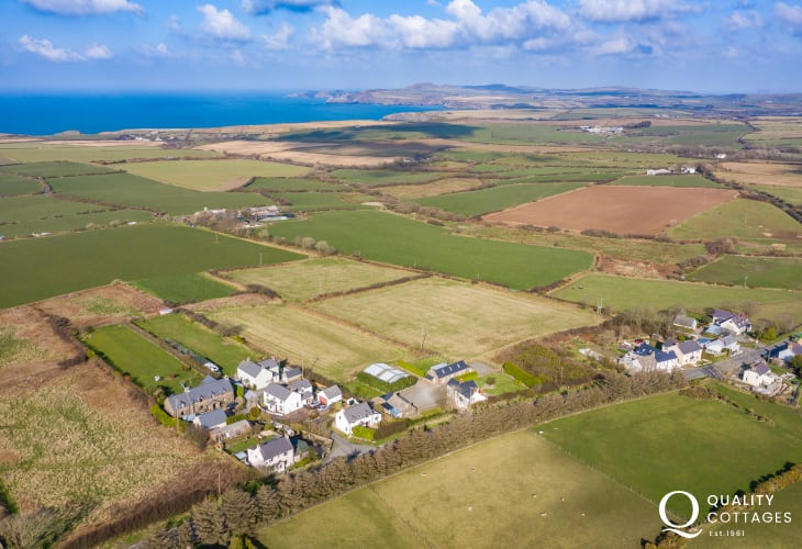 Drone view of temple cottage, barn and house and out over to coastal views