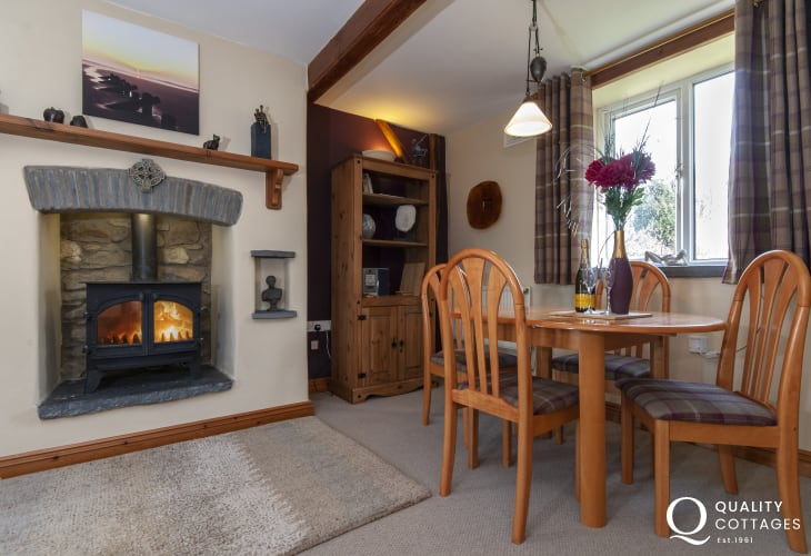 Coastal cottage Pembrokeshire - dining area with gas effect log burner