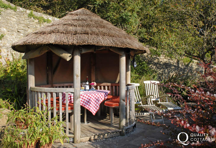 Escape to the little thatched gazebo in the gardens at Slade Cottage