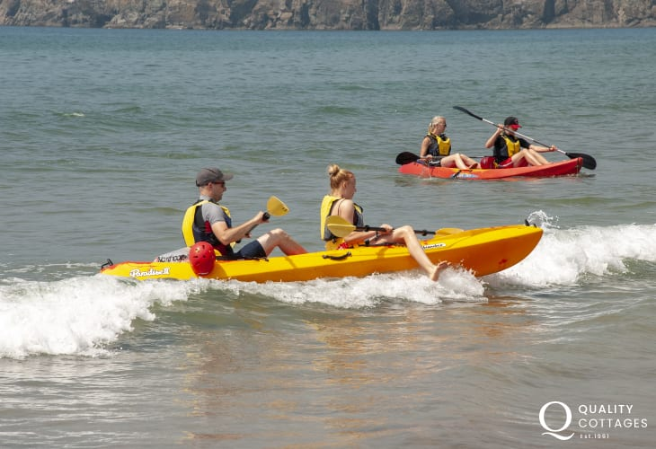 Catching the waves at Newgale - a full hire service for wet suits, surf boards and kayaks is available at 'Newsurf'