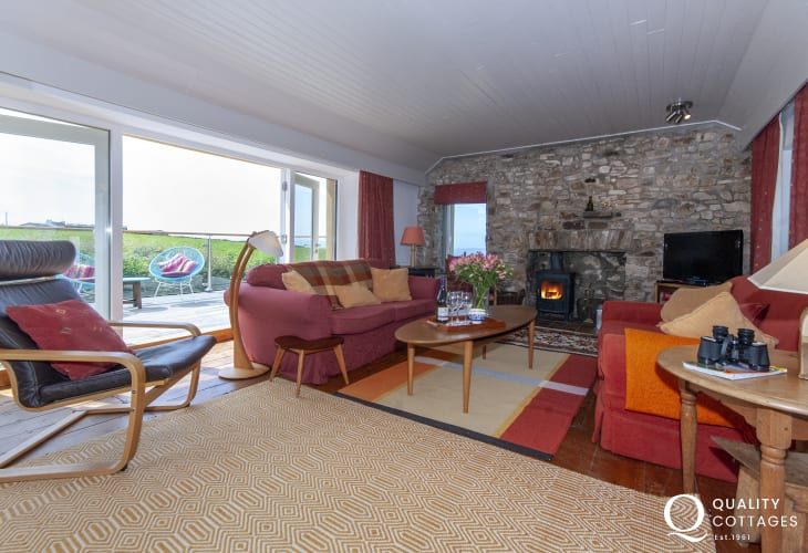 Druidstone Farmhouse holiday home - lounge with patio doors to deck, sea views and wood-burning stove