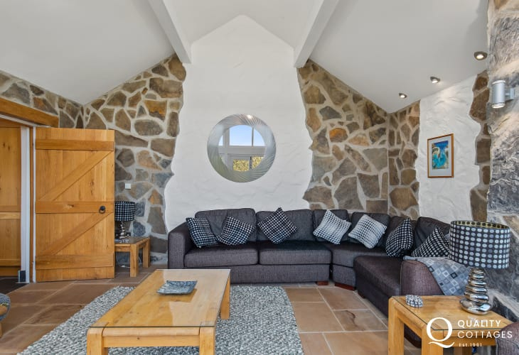Stonework walls and L-shape sofa in holiday cottage Pembrokeshire