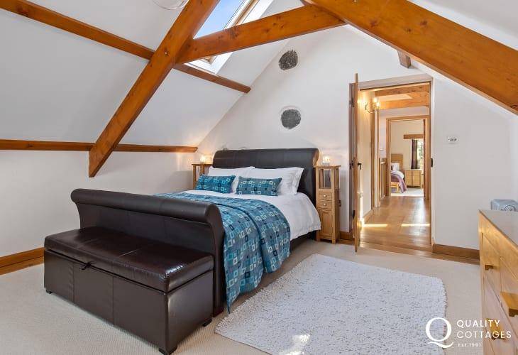 Kingsize sleigh bed in bedroom with oak beams