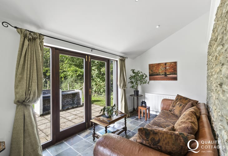 Aberporth cottage holiday seating area leather sofa with French doors opening to garden