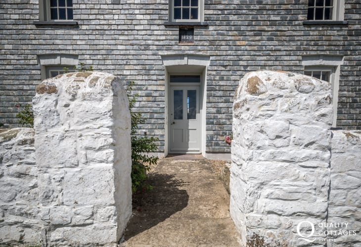 Farmhouse entrance is hung with slates , surrounded by whitewashed walls
