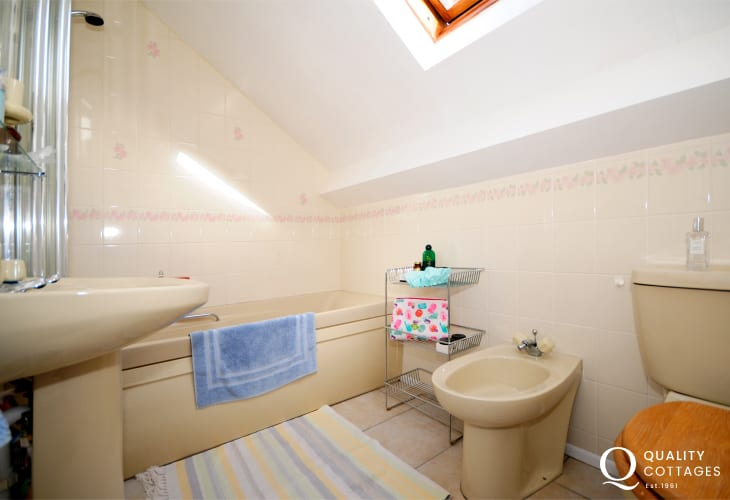 Harlech holiday cottage - family bathroom with WC, wash basin, bath and over bath shower.