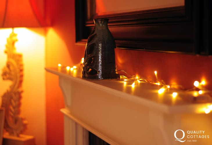 Holiday cottage North Wales on the Llyn Peninsula  - sitting room with original fireplace and string lights.