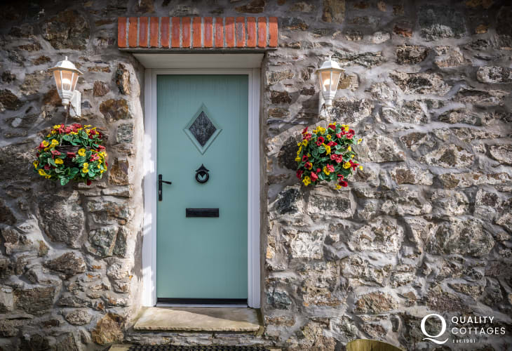 Stonewoork, hanging baskets and front door at Farrier's Cottage