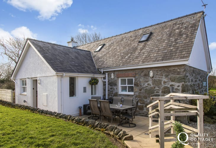 Rear exterior shot of holiday cottage with patio and dining furniture