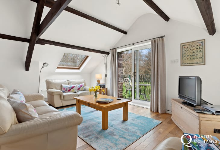 Beamed living room with 2 and 3 seater sofas with private balcony with stunning rural views
