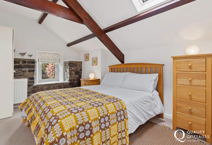 Beamed master bedroom with original stonework, oak furniture and traditional Welsh woollen blanket