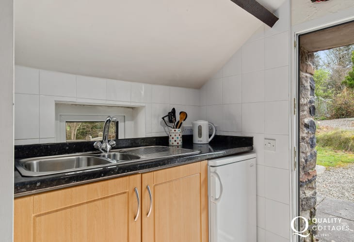 Shaker Kitchen with sink, fridge and kettle with doorway and stairs leading to grounds.