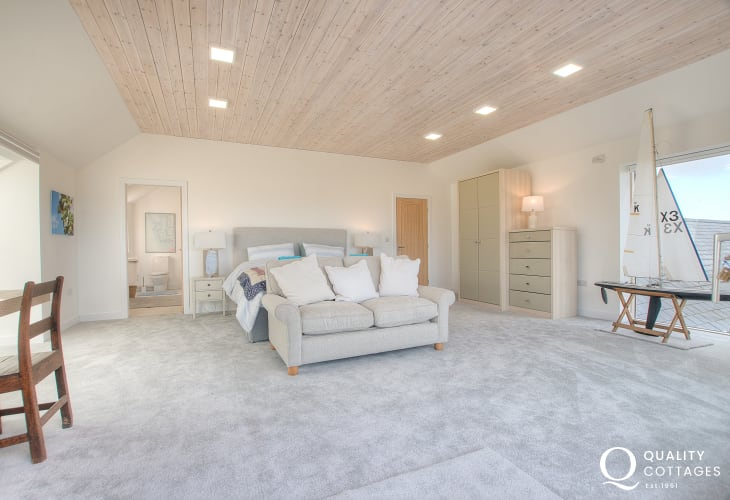 Luxury coastal holiday cottage - main bedroom with king size bed, ensuite and balcony overlooking Red Wharf Bay, North Wales.