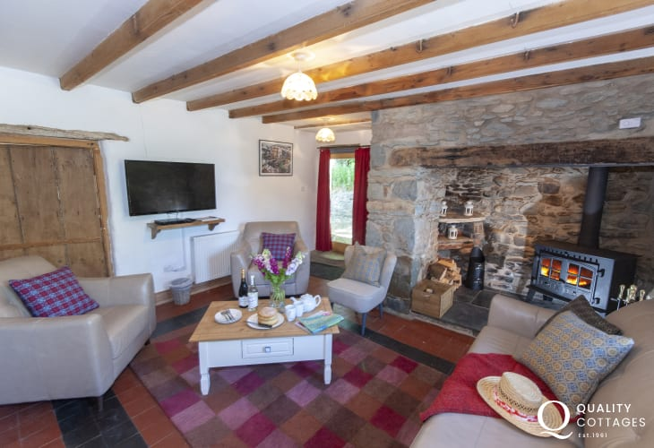 Solva holiday farmhouse - spacious sitting room with multi-fuel stove and door to the gardens