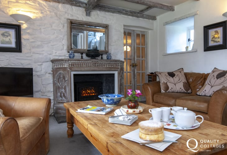 Cosy living room with large comfy sofas and electric effect wood burning stove