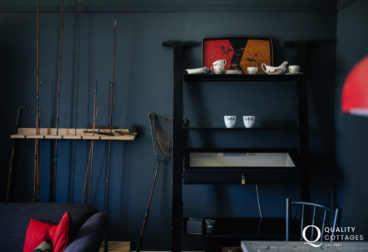 Sitting room sofas, shelving artefacts fishing rods