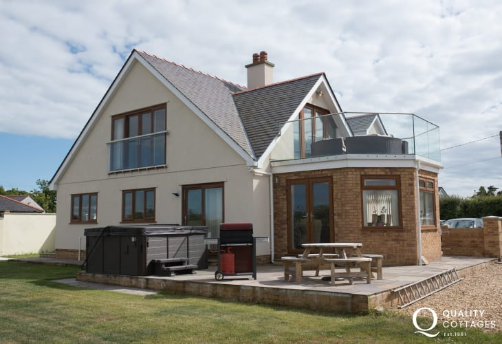 Exterior of holiday cottage garden with hot tub, patio seating, balcony, BBQ and sea views, in Four Mile Bridge, Anglesey.