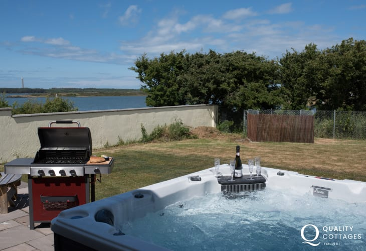 Four Mile Bridge coastal holiday cottage in Anglesey - hot tub and barbecue overlooking the sea.