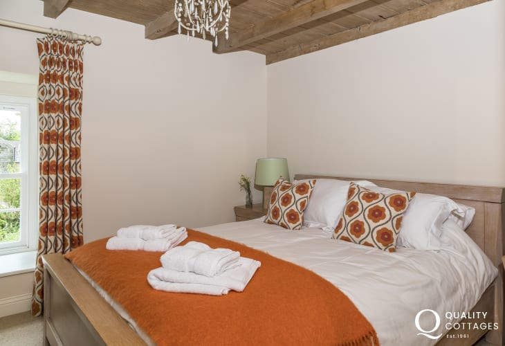 Bedroom with kingsize bed, bedside tables and lamps in farmhouse holiday cottage, sleeping 12 in Newport, Pembrokeshire.