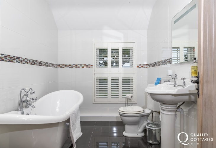Family bathroom with roll-top bath, WC and heated towel rail - holiday cottage in Newport, Pembrokeshire, sleeping 12 people.