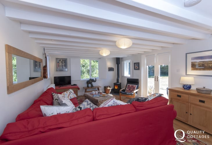 St Davids City holiday cottage - cosy sitting room with log burning stove and doors to the garden