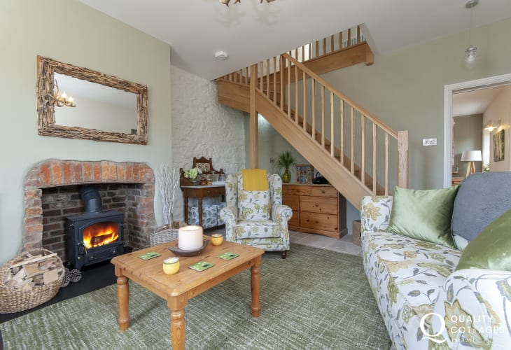 Pembrokeshire holiday home - cosy sitting room with solid Oak staircase and wood burning stove