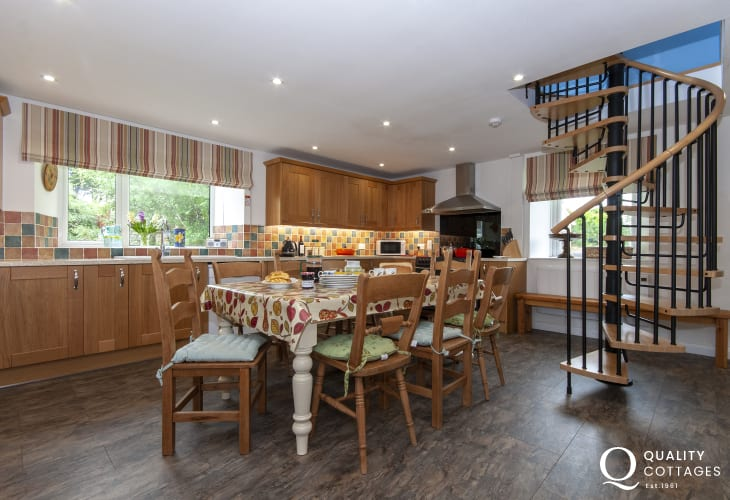 Solva self catering family home - modern kitchen/diner with spiral staircase to the loft