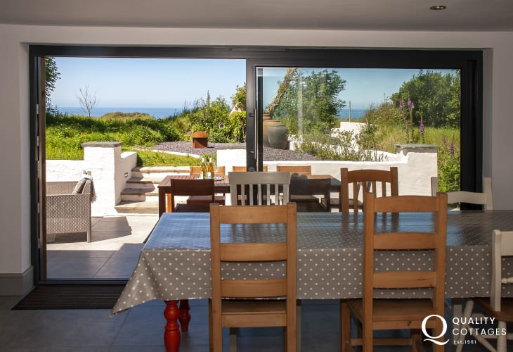 Holiday cottage near Porthgain on the St. Davids Peninsula - Dining area with sliding glass doors to the patio and garden