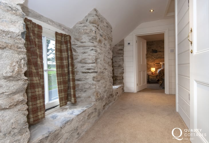 Exposed stone walls in renovated traditional Pembrokeshire holiday cottage with sea views, near St. David's