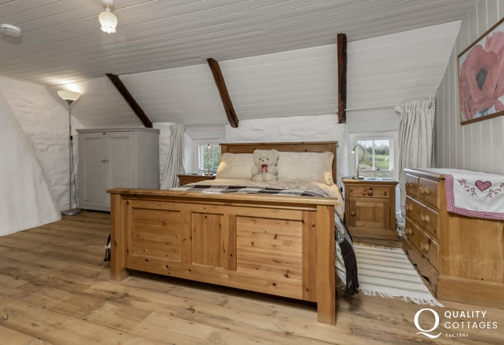 Cottage holiday nearby Pencastell Motte - master bedroom ensuite 2 wooden chests bedside cupboards
