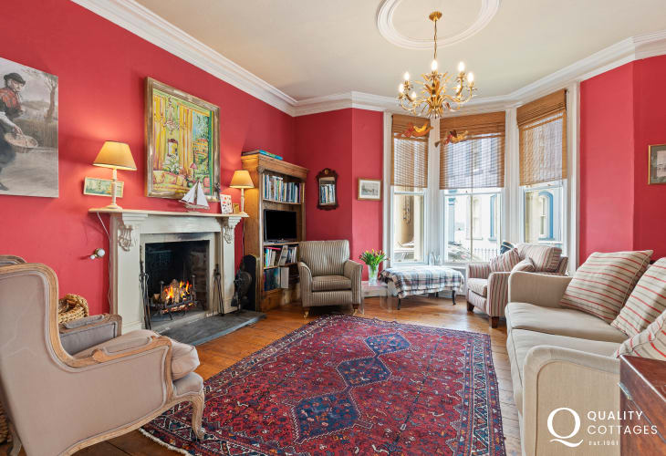 Setting room sympathetically decorated in bold Victorian red and traditional style furniture with open log fire