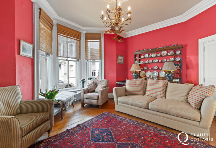 Sitting room on the ground floor, sympathetically decorated in bold Victorian red and traditional style furniture with open log fire