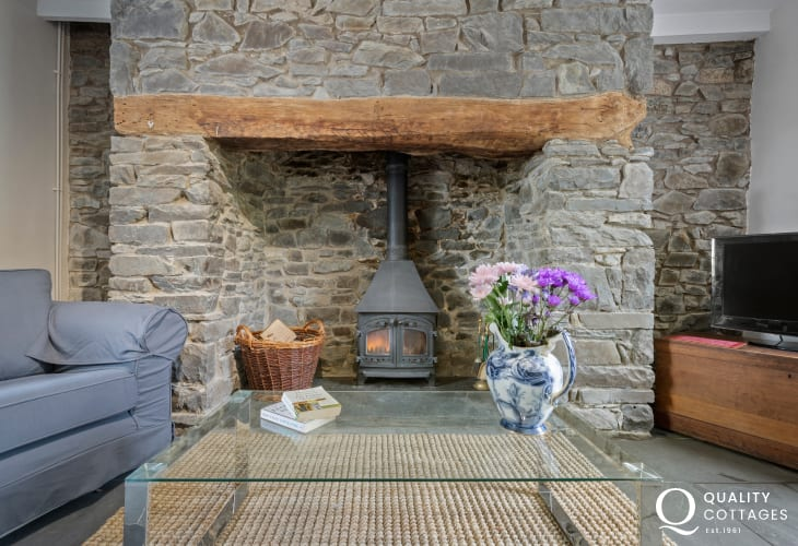 Lounge with attractive inglenook fireplace housing a wood burner, ideal for cosy winter nights
